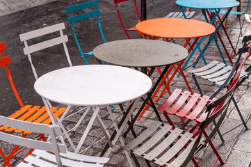 Cafe tables and chairs outside on rainy day