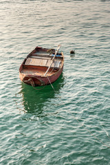 Single rowing boat floating on green water