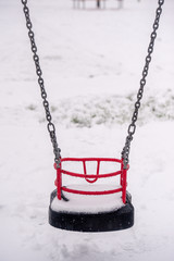 Snow on swing seat in a children's playground