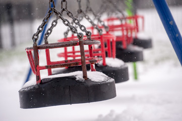 Snow on swing seat in a children's playground