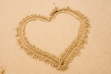 Heart shape drawn in the sand on a beach