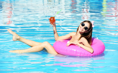 Young woman enjoying with rubber ring and cocktail in swimming pool at summertime