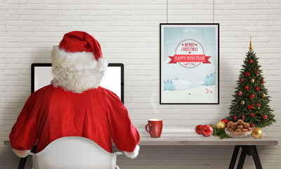 Santa Claus responds to letters on a computer for Christmas. Gifts, Christmas tree and decorations on table.