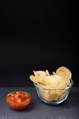 Crispy potato chips with sea salt in glass bowl, tomato sauce, on stone board, black background, space for text.