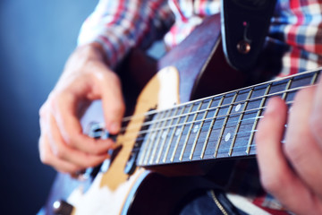 Young man playing on electric guitar close up