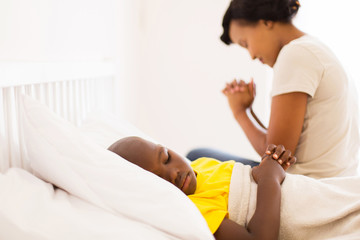african sick little boy lying in bed with his mother praying