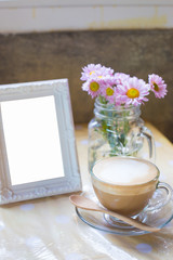 hot coffee and bouquet of flower and blank white photo frame on grunge wood table.