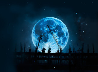 Construction site with cranes and workers under  full blue moon at night