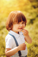 cute happy long hair toddler boy eating cookie outdoor on sunny summer walk