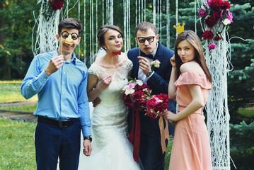elegant stylish happy guests and bride and groom having funny ph