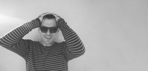 Portrait of happy hipster wearing sunglasses against color backg