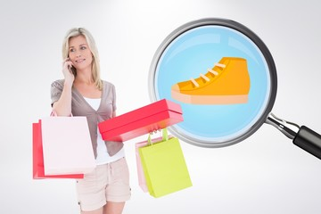 Composite image of happy blonde with shopping bags on the phone