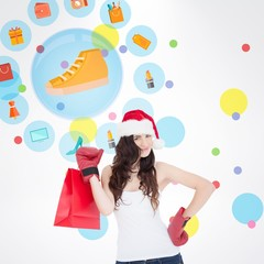 Smiling blonde woman with santa hat  standing with shopping bag