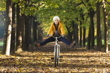 Happy smiling girl riding a bicycle at the park