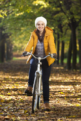 Smiling woman standing with a vintage bicycle at the park