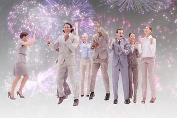 Euphoric business team jumping against firework
