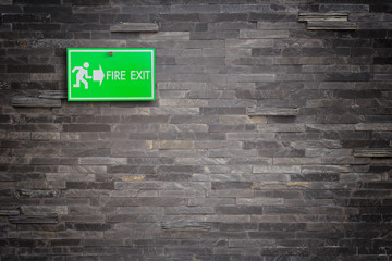 Green fire exit sign on stone wall