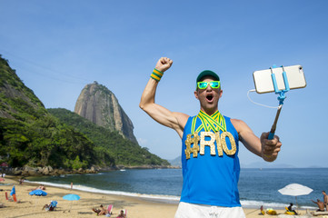 Rio hashtag gold medal athlete posing for a selfie with his mobile phone on a selfie stick at Praia Vermelha Red Beach in Urca