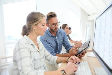 Student girl with teacher working on desktop computer
