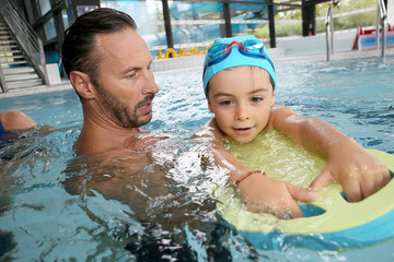 Boy child learning to swim with trainer