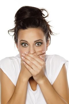pretty embarrassed young woman covering her mouth with her hands