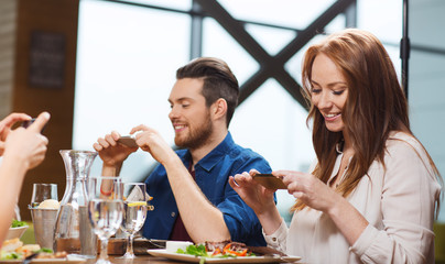 happy friends taking picture of food at restaurant