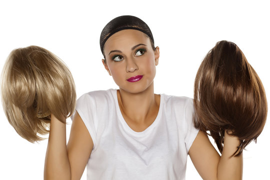 young woman with a wig cap make a comparison between two wigs