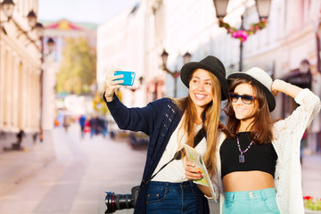Two happy girls taking selfies with mobile phone