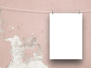 Single hanged paper sheet frame on the right with clothes pin on pink cracked and scratched plastered concrete wall background