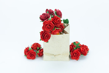 Gift and red roses on white isolated background