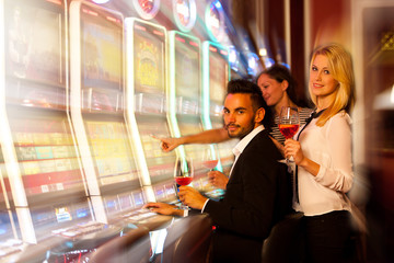 four young people playing slot machines in casino