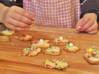 young girl decorating butter cookies with sprinkles