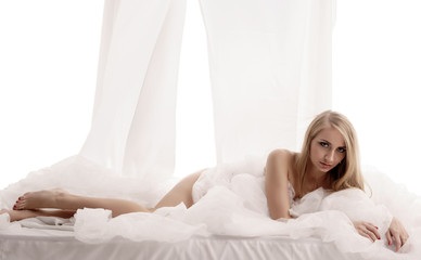 Erotica. Studio image of seductive blonde in bed