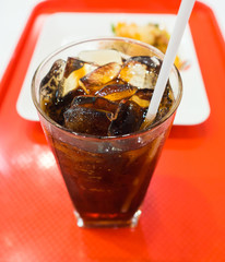 Close up of a cup of soft drink on the red tray with blurry food dish background