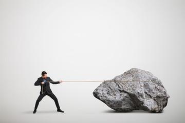 businessman in formal wear pulling the big stone