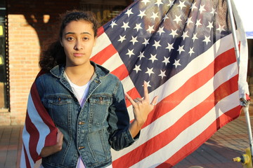 Beautiful ethnic teenage girl in front of a flag of the U. S.