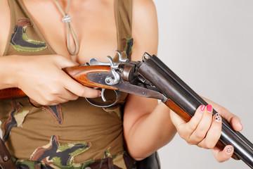 Hands girl charging a gun. Gray background. close-up.