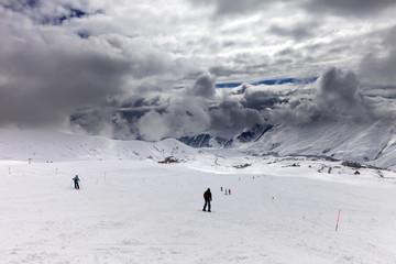 Skiers on ski slope before rain