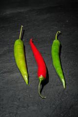 Zwei rote und eine grüne Peperoni auf einem Untergrund aus dunklem Naturschiefer
