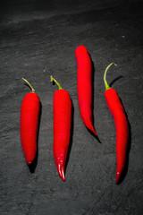 Drei rote Peperoni auf einem Untergrund aus dunklem Naturschiefer