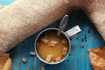 Mug of soup and napkin on blue wooden background