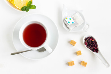 Tea set with a cup of tea, lemon, filter in teapot-shaped bowl, cube sugar and flowers. White background, top view