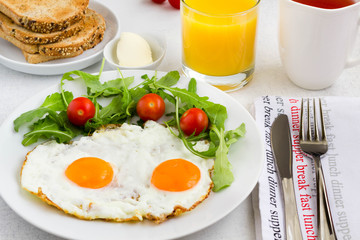 Fried egg with vegetables, fresh orange juice, a cup of tea and toast.