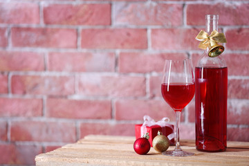 Bottle of red wine and glass with christmas gifts on wall background