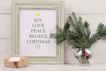 Christmas poster in  shabby chick frame,  fir branch and vintage gift box with with copy space blank tag on white background. Scandinavian style home interior decoration