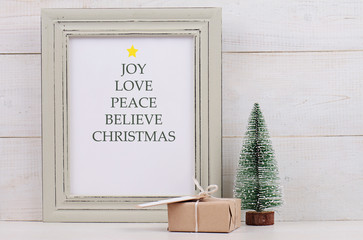 Christmas poster in  shabby chick frame, fir and vintage gift box with with copy space blank tag on white background. Scandinavian style home interior decoration