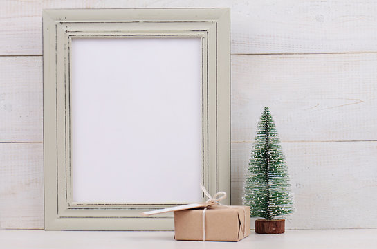 Christmas and New Year background. Empty picture frame, fir and vintage gift box with with copy space blank tag on white background. Copy space image. Scandinavian style home interior decoration