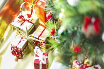 Christmas decoration with gifts and present boxes under a pine tree.