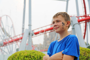 Boy on a background of rollercoaster at an amusement park