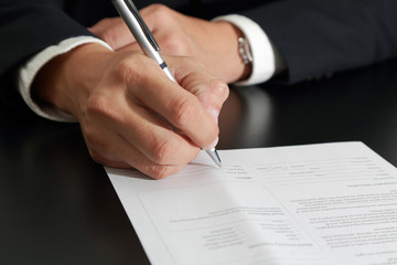 Businessman's Hand holding a pen signing to the document